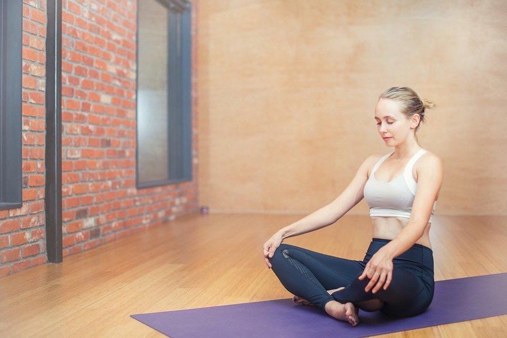 Woman doing meditation on a yoga mat