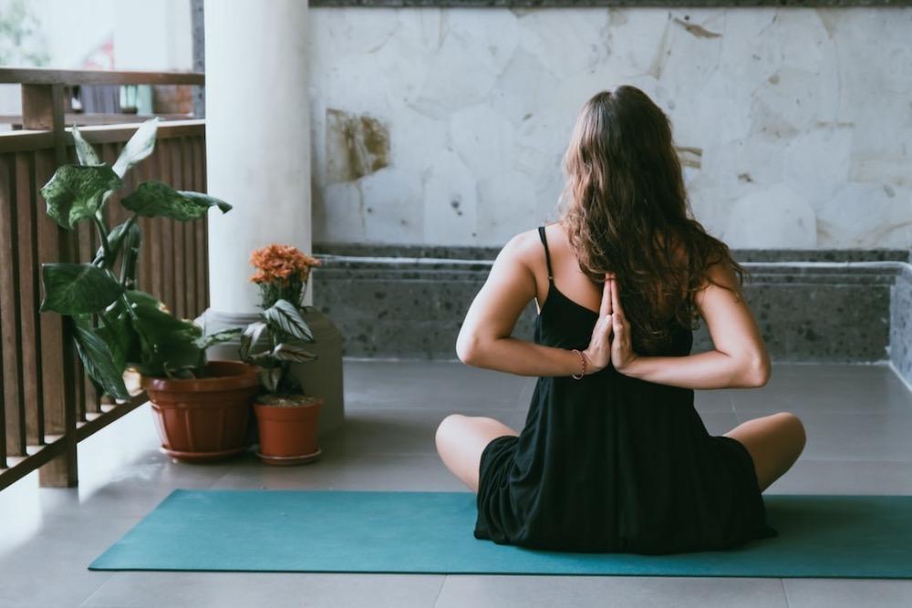 Woman practicing yoga on blue yoga mat