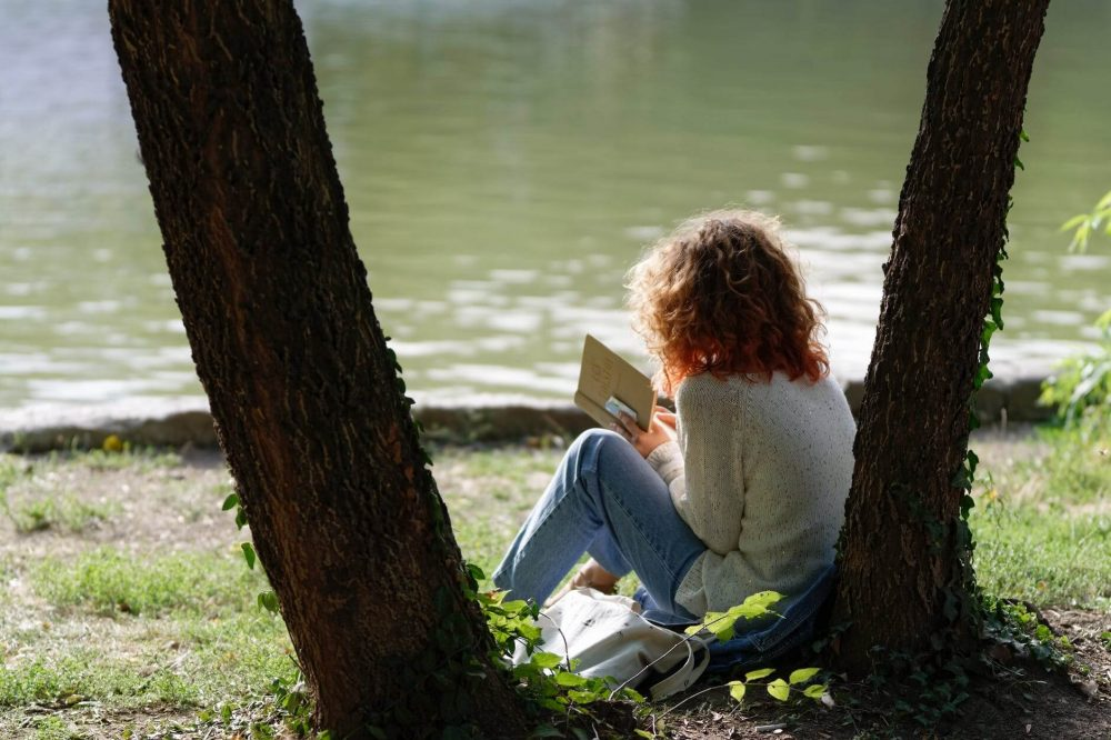 Woman reading a book near a lake