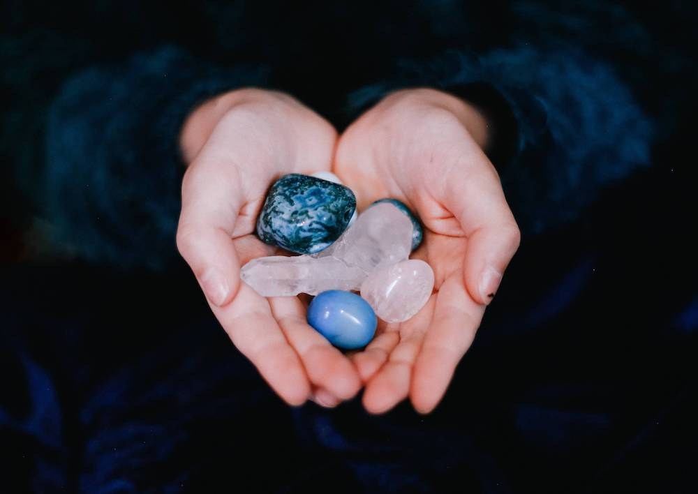 lots of gemstones in hands - yoga retreat home